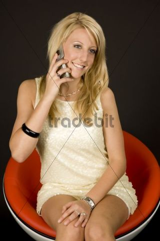 Young blonde woman talking on a cell phone