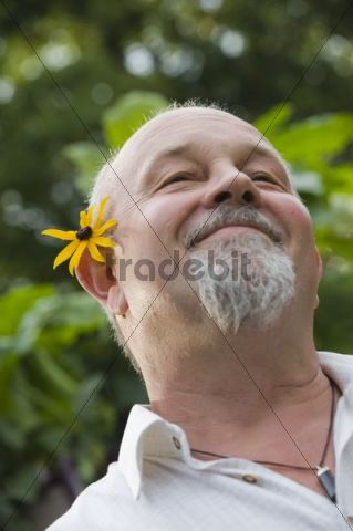 Smiling elderly man with flower behind his ear