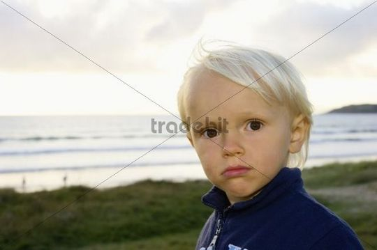 Little boy standing confidently on a dune near the sea, Brittany, France, Europe