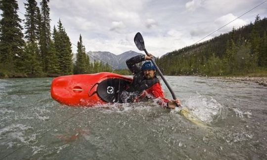 White water kayaking, man paddling a play boat, stabilizing boat, high brace, mountains, coastal range behind, Wheaton River, Yukon Territory, Canada
