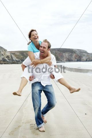 A man carrying a woman piggy back on the beach