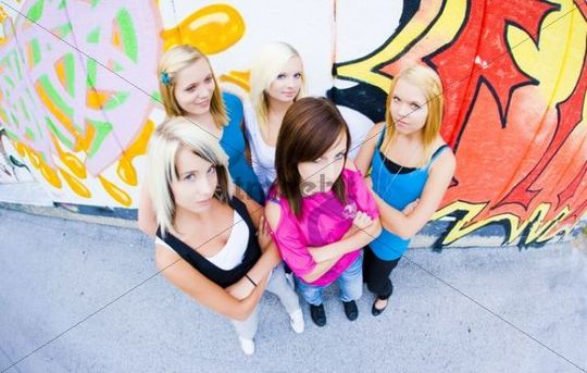 Group of teenage girls in front of a graffiti wall