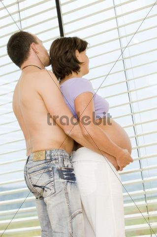 Expectant parents, man and pregnant woman standing at the window