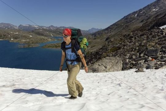 Young woman hiking, backpacking, hiker with backpack, snow field, descending towards summit of historic Chilkoot Trail, Chilkoot Pass, Crater Lake behind, alpine tundra, Yukon Territory, British C