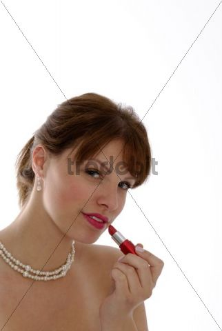 Young woman is putting on red lipstick