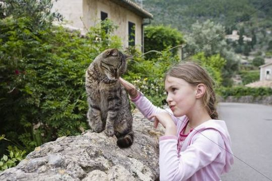 Girl, 8 years, caressing a cat, Deià, Mallorca, Majorca, Balearic Islands, Spain, Europe