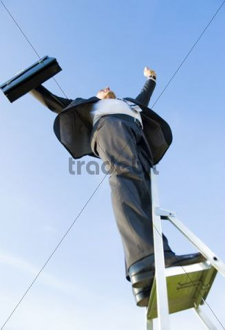 Businessman climbing a ladder, symbolic image for the career ladder