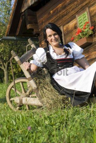 Young woman wearing a Dirndl dress sitting on a wheelbarrow on a farm