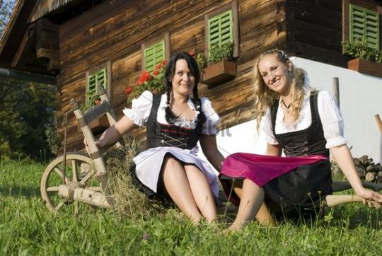 Two young woman wearing Dirndl dresses sitting on a wheelbarrow on a farm