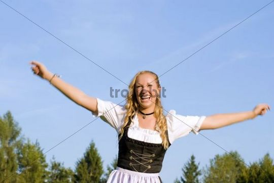 Happy, young woman wearing a Dirndl dress