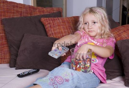 Girl with sweets and remote control watching TV