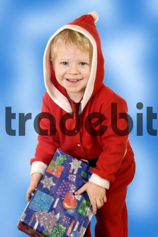 A little boy in the guise of Santa Claus