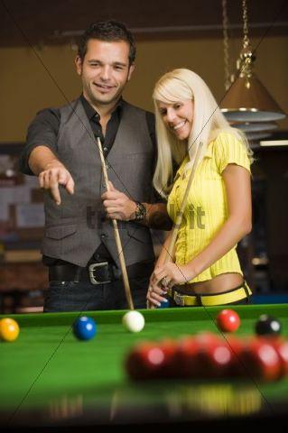 Man and woman playing billiard