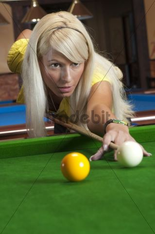 Young blonde women playing snooker