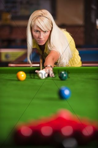 Young blonde woman playing snooker