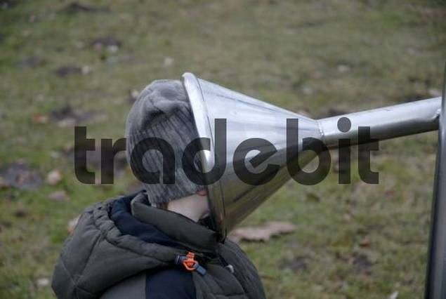 curious little boy sticking his head into the funnel of an intercom,