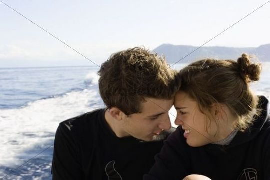 Young couple sitting at the stern of a small boat, Isola Eolie, Sicily, Italy, Europe