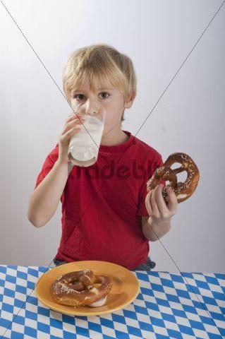 Boy, 4-5 years, with pretzel and Gelbwurst yellow sausage, drinking milk