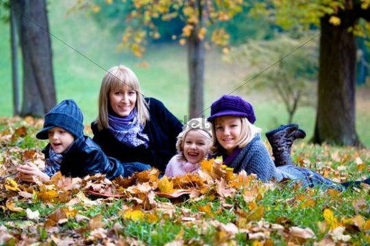 Mother and three children in a park in autumn