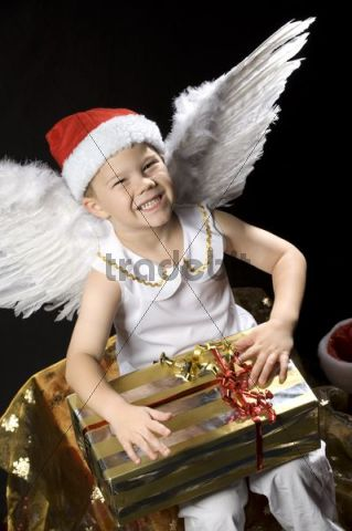 Boy dressed as Christmas angel with Christmas present