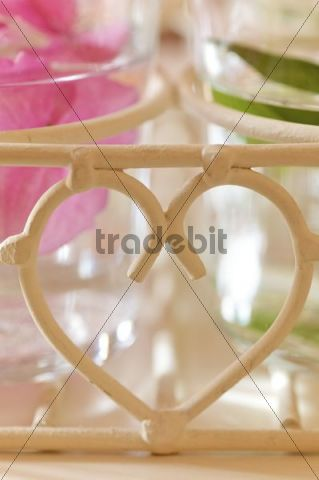 Flowers in glasses of water, heart-shaped decoration