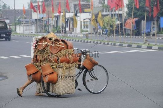Potter transporting his pottery to market place by bike, Yogyakarta, Central Java, Indonesia, Southeast Asia, Asia