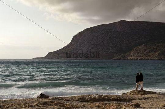 Couple looking out to sea, Adia Bay, island of Karpathos, Aegean Islands, Dodecanese, Aegean Sea, Greece, Europe