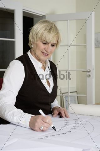 An architect sitting at the desk in her office, sketching a plan