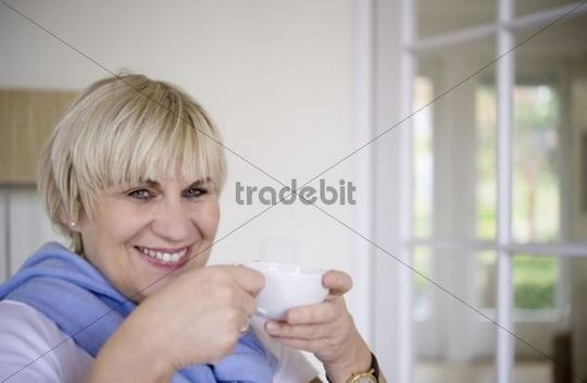 A woman is sitting and drinking from a cup of tea in her office