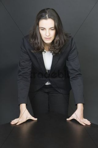 Strategy, business woman leaning on a black table, looking defiantly