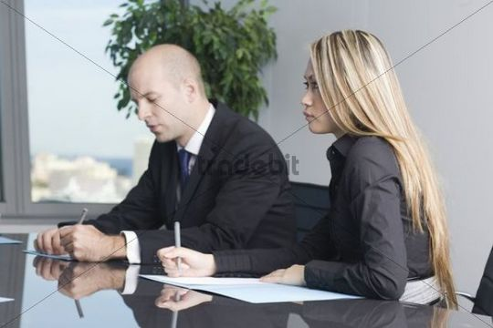 Young Asian business woman listening at a customer meeting, taking notes