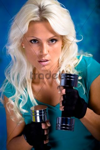 Young woman doing fitness exercise with dumbbells