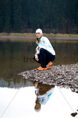 Young woman having a break at a forest lake during jogging