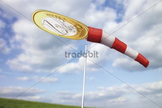 Windsock filled with a squashed one euro coin in front of clouds in the sky, symbol image