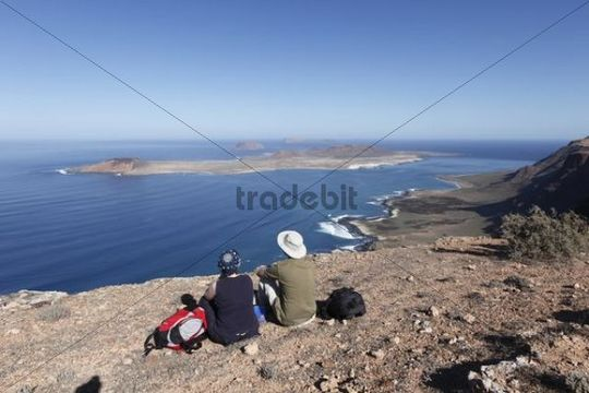 Hikers resting at Risco de Famara near Guinate, in front of the islands of La Graciosa, Montaña Clara and Alegranza, Lanzarote, Canary Islands, Spain, Europe