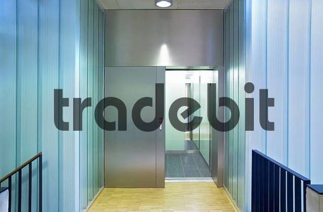 elevator in a modern building, mixed construction material glass, wood, metal