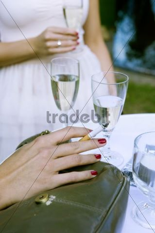 Hand of a young woman holding a cigarette, another holding a glass of champagne at a Hollywood costume party