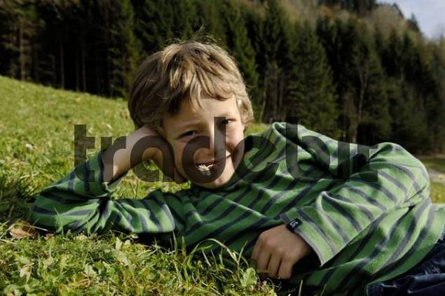 Nine-year-old boy lies relaxed in a meadow