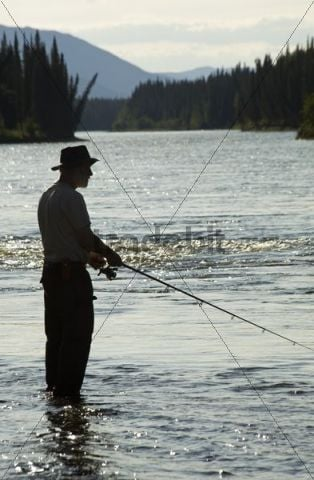 Silhouette of man fishing upper Liard River at sunset, standing in shallow water, mountains behind, Yukon Territory, Canada