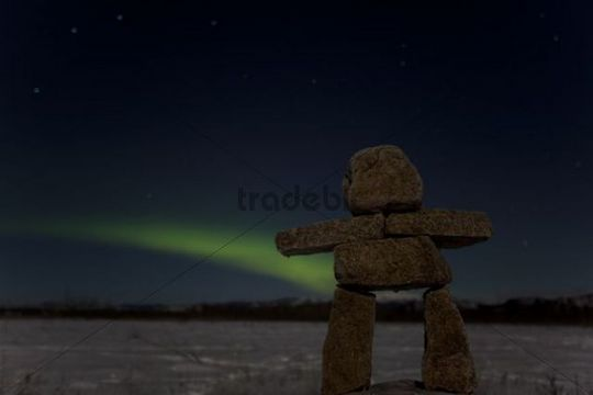 Inuit stone man, inukshuk, stone landmark or cairn, green Northern Lights, Polar Lights (Aurora borealis), near Whitehorse, Yukon Territory, Canada