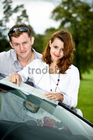 Young couple looking at a road map on a car