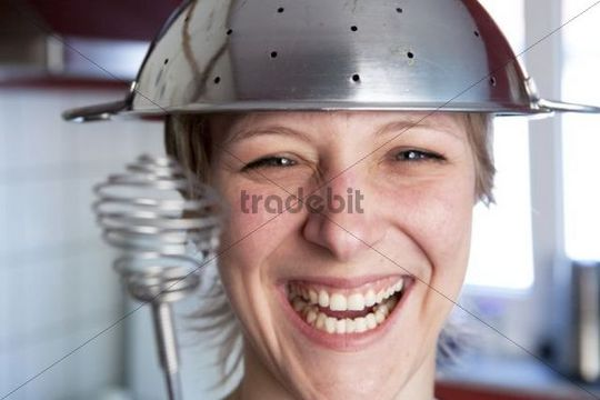 Smiling woman in a kitchen with a kitchen sieve on her and a whisk in her hand playing a cooking duel
