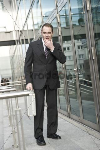 Manager standing in front of an office building