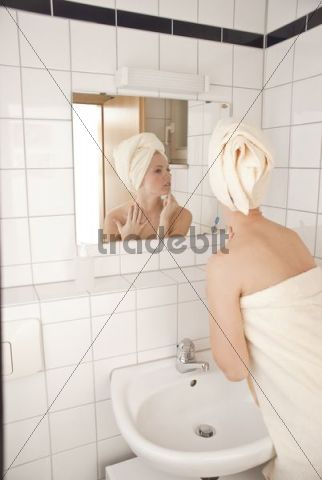 Woman in the bathroom in front of a mirror, judging her face