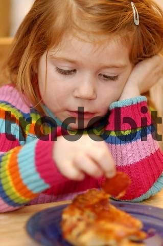 girl 4 years old eating pizza playing with food