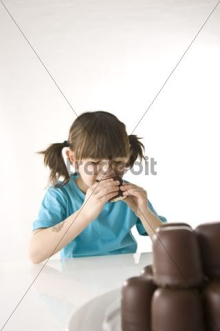 Little girl biting into a chocolate marshmallow with relish