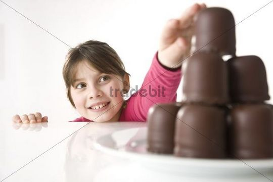A girl reaching secretly for a chocolate marshmallow