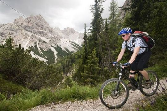 Mountain biker on trail in front of Mt Seekofel, South Tyrol, Italy, Europe