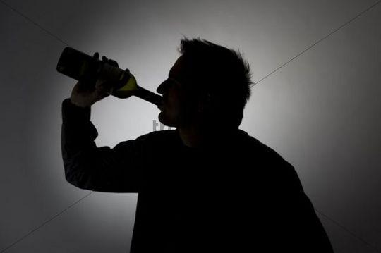man drinking from a wine bottle  silhouette