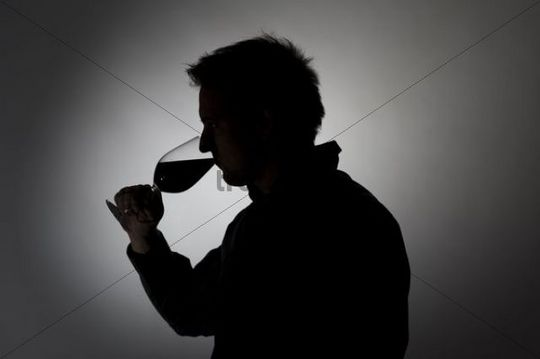 Man drinking from a wine glass, silhouette